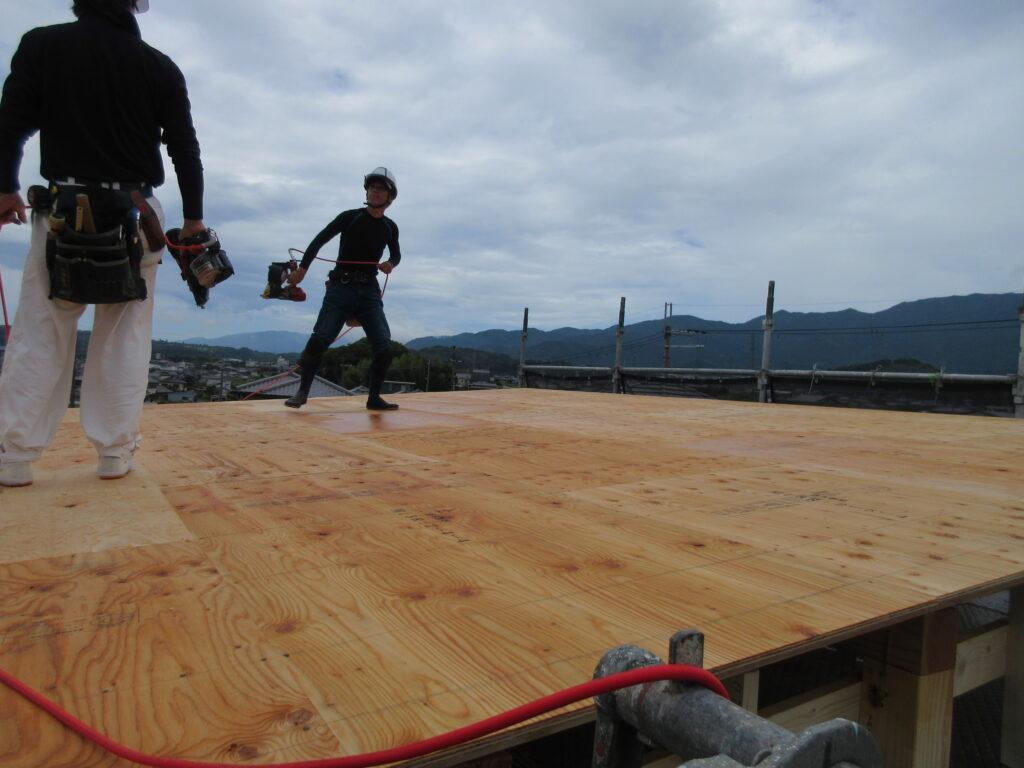 大屋根の板にビスを打っています(曇り空)